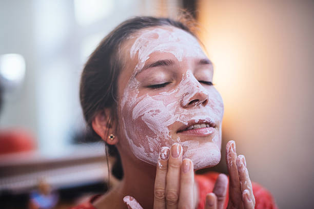 Femme qui s'applique un masque d'argile blanche sur le visage