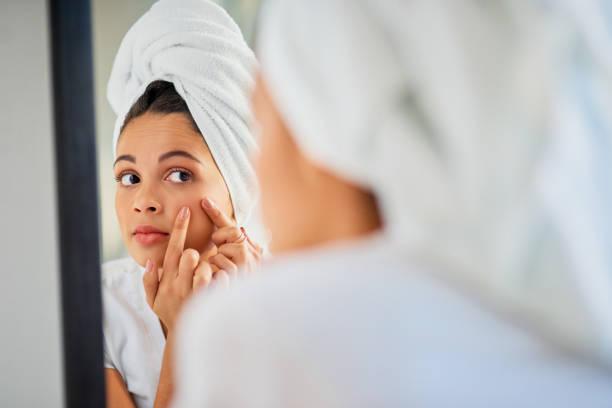 Jeune femme qui examine sa peau dans un miroir