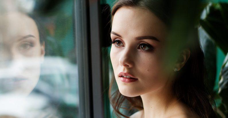 Jeune femme brune qui regarde par la fenêtre